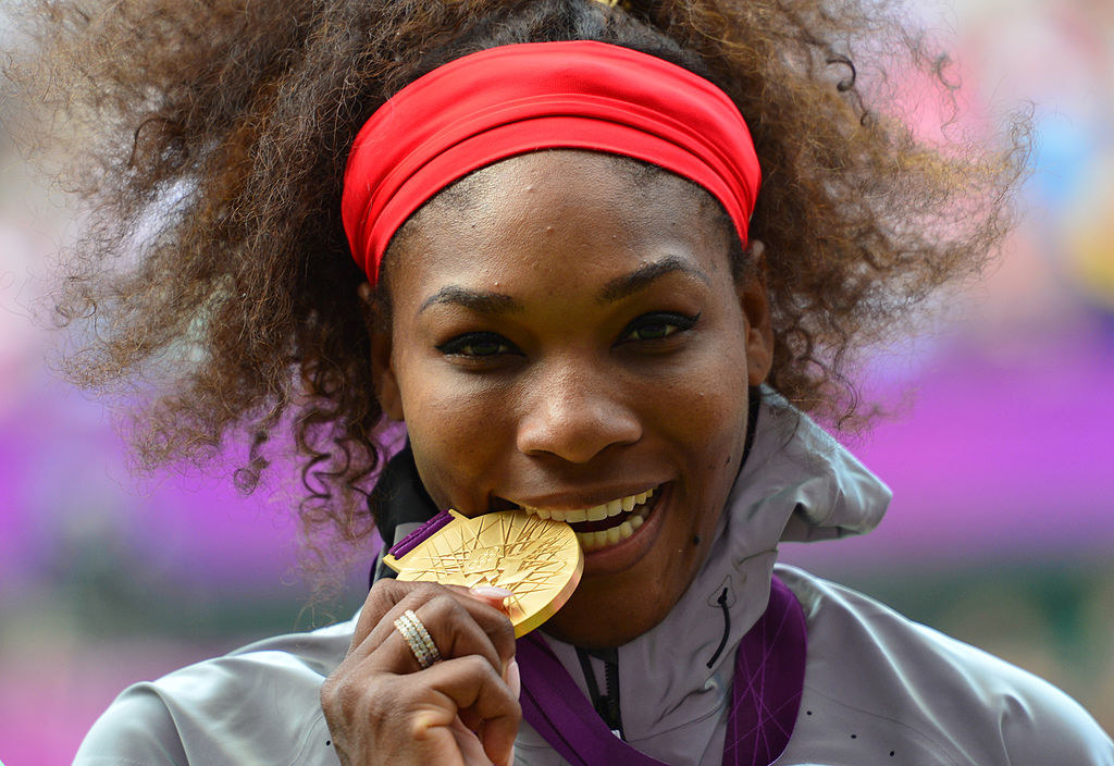 Serena Williams poses on the podium with her gold medal after defeating Russia's Maria Sharapova in the women's singles gold medal match