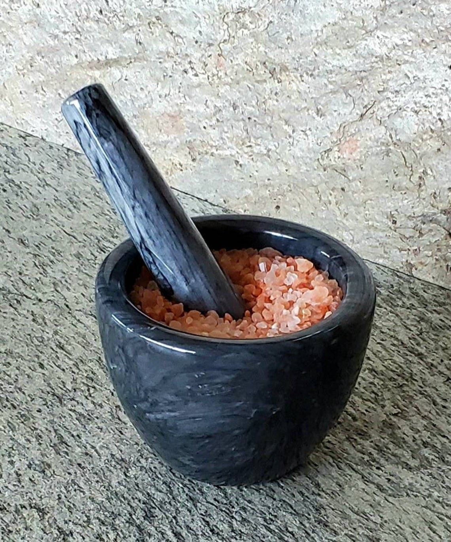 Dark marble mortar and pestle with salt inside