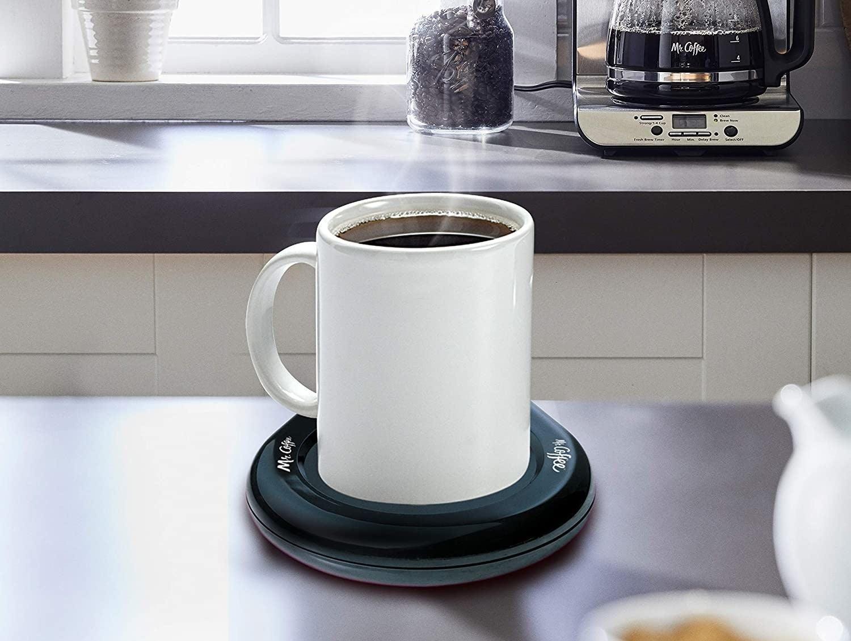 Mug propped on black circular warmer on table