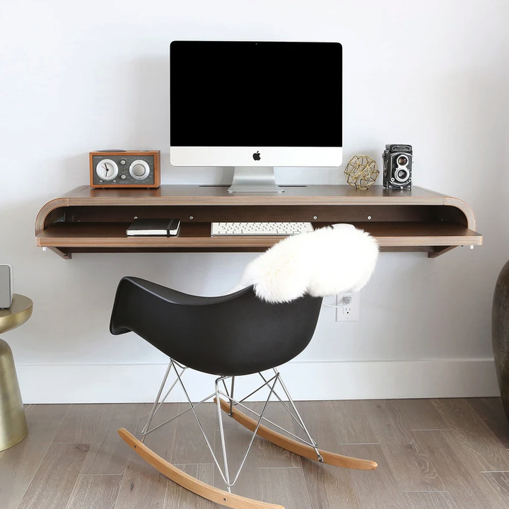the floating desk with a computer on it and some decor items