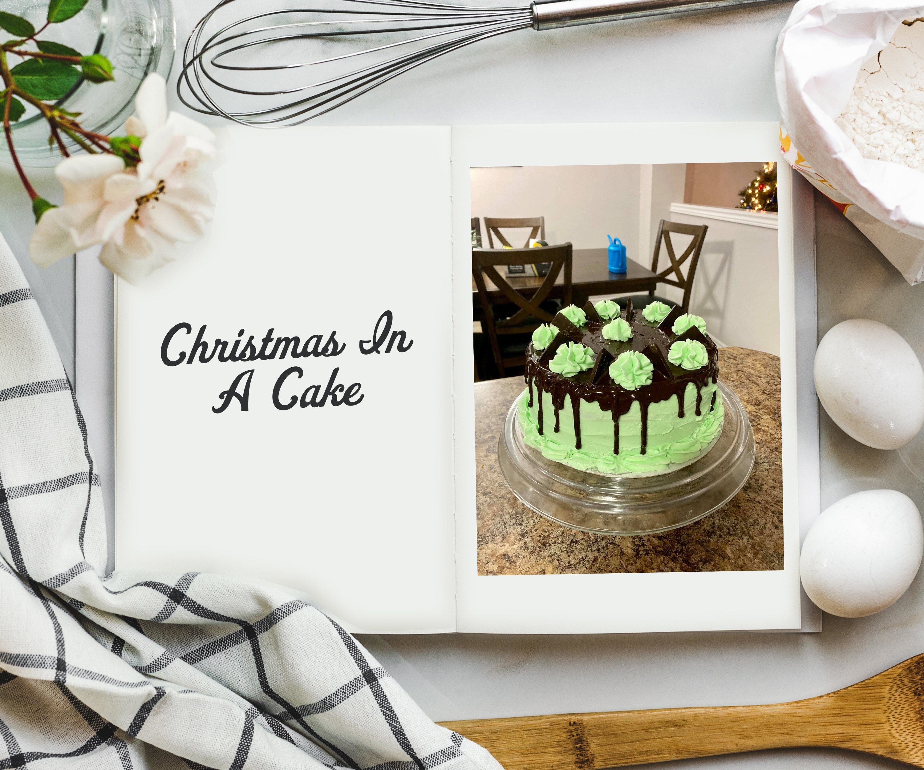 An overhead shot of cookbook on a table surrounded by ingredients and a photo on the inside of a lime green cake on a cake-stand covered with chocolate ganache on top and piped green florets.