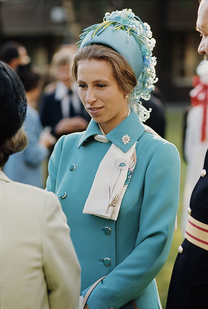 A young Princess Anne wearing a decorated pill box hat as she listens to someone speak