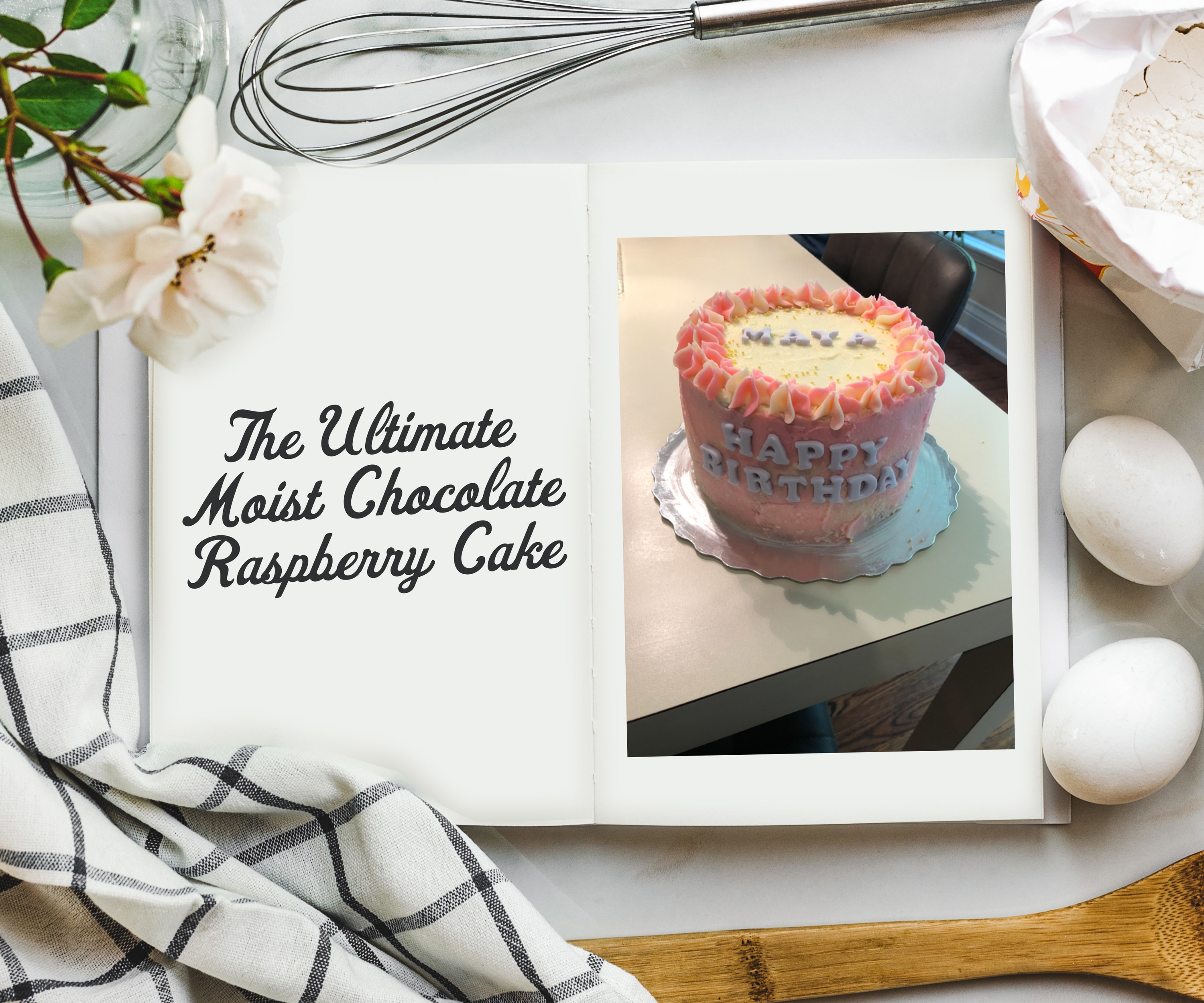 An overhead shot of cookbook on a table surrounded by ingredients and a photo on the inside of a multi-tiered cake that says Happy Birthday on the side. It's covered in pink and white frosting.