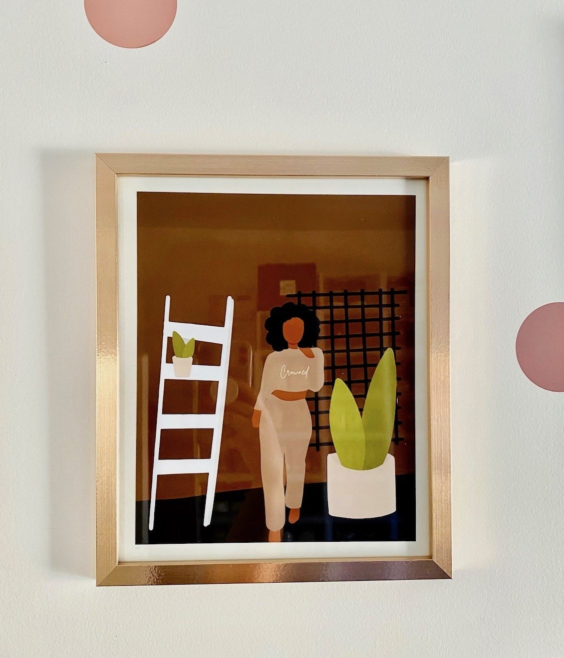 """A framed print of an illustrated Black woman wearing a sweatshirt that says """"crowned"""" while standing next to plants"""