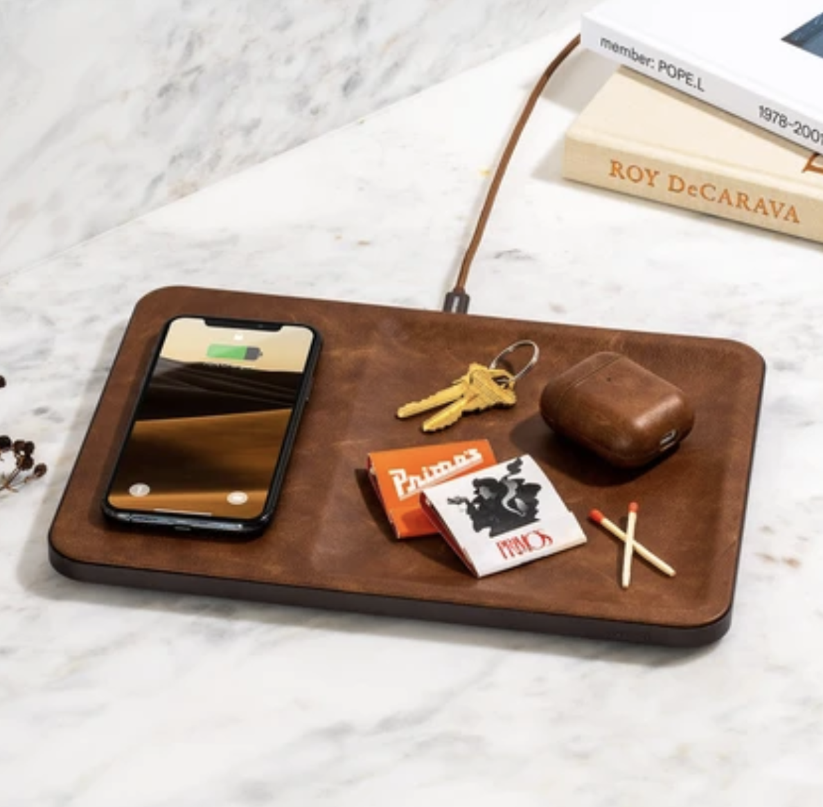 Rectangular wireless charging pad that looks like brown leather with a spot to charge devices and space to hold small items