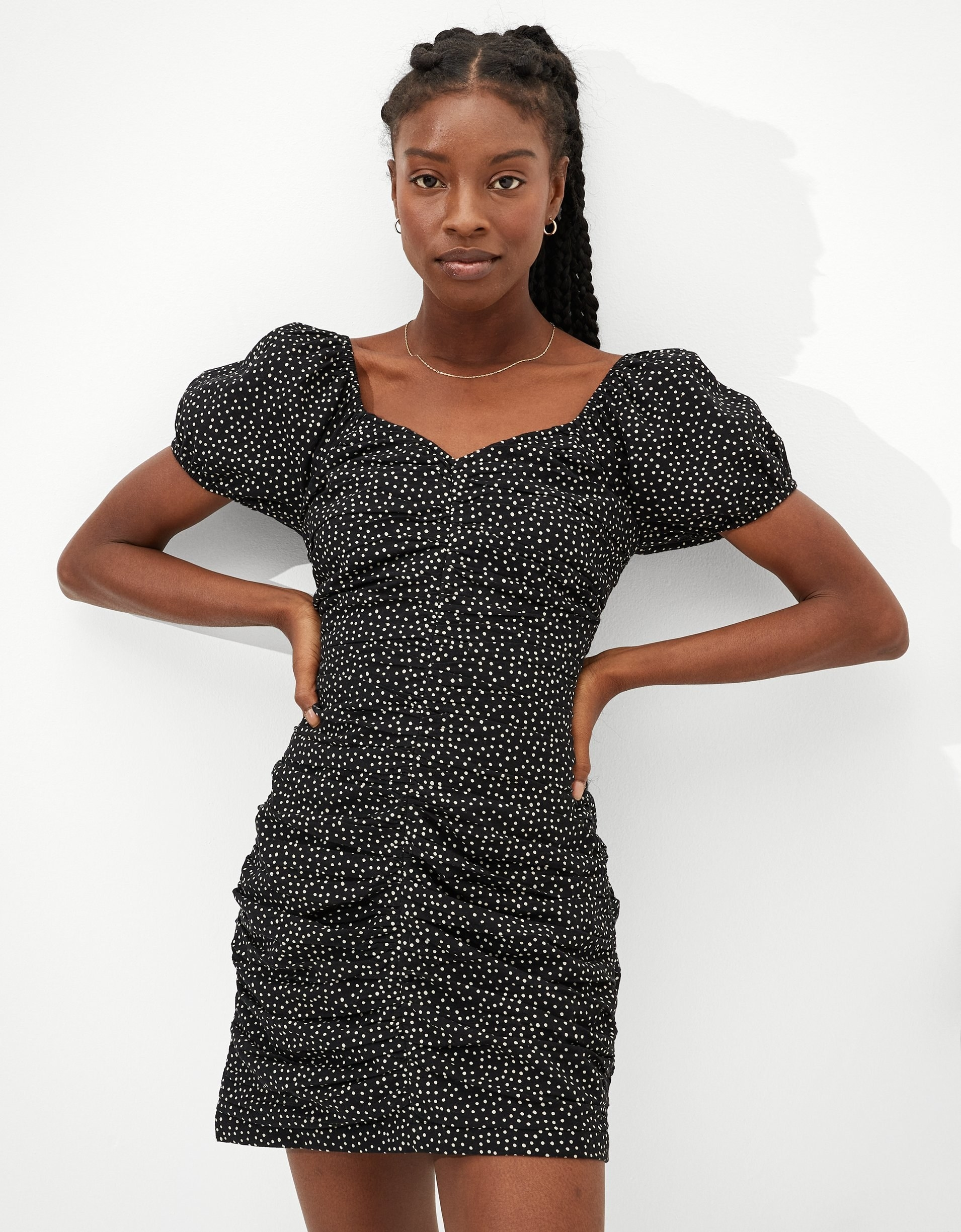 model wearing ruched midi dress with puff sleeves