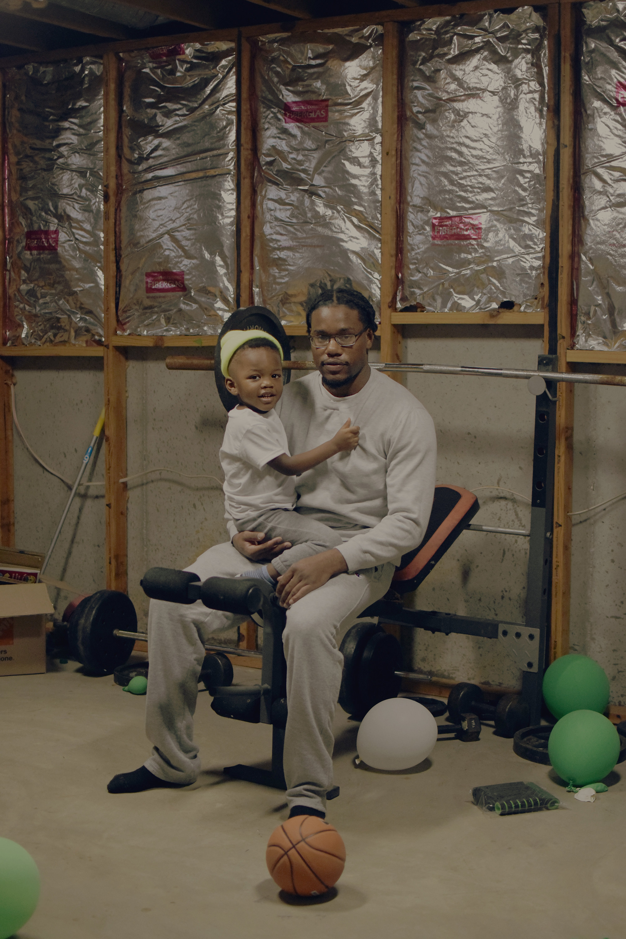 A man in a home gym holding a toddler