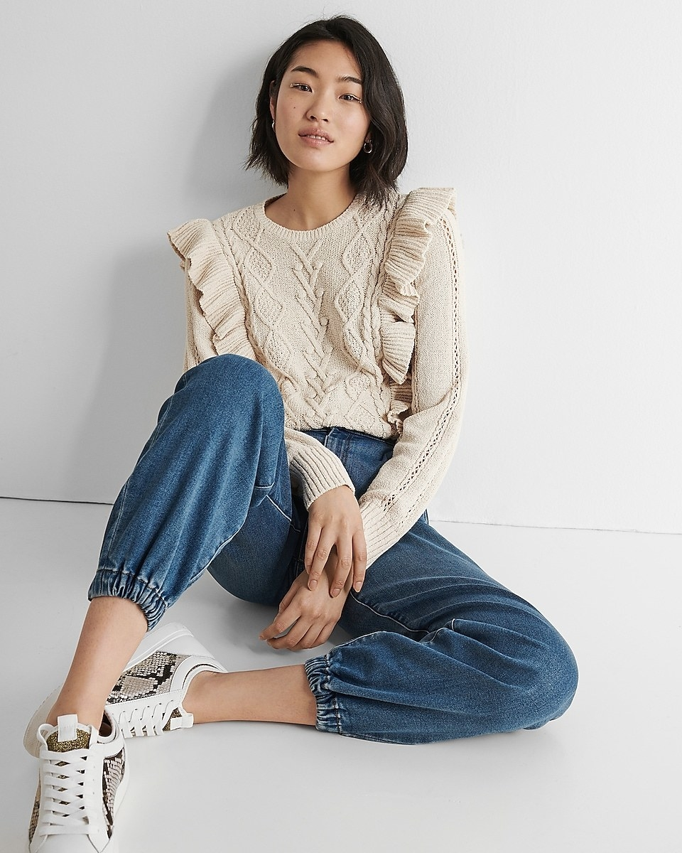 model wearing cable knit ruffle sweater