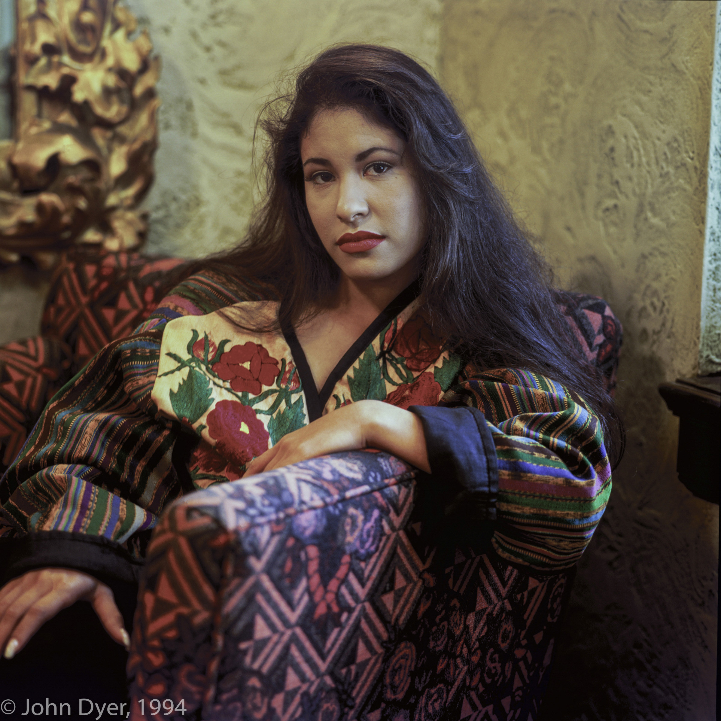 selena quintanilla posing for the camera while wearing a floral striped jacket, she is sitting down on a patterned chair