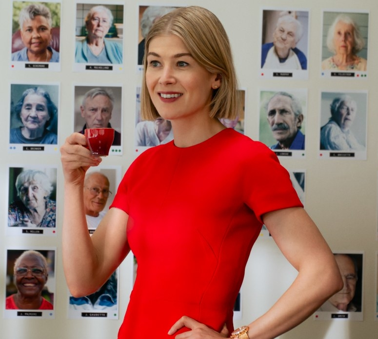 A woman with a small mug in her hand grins in front of a wall of photos featuring elderly people.