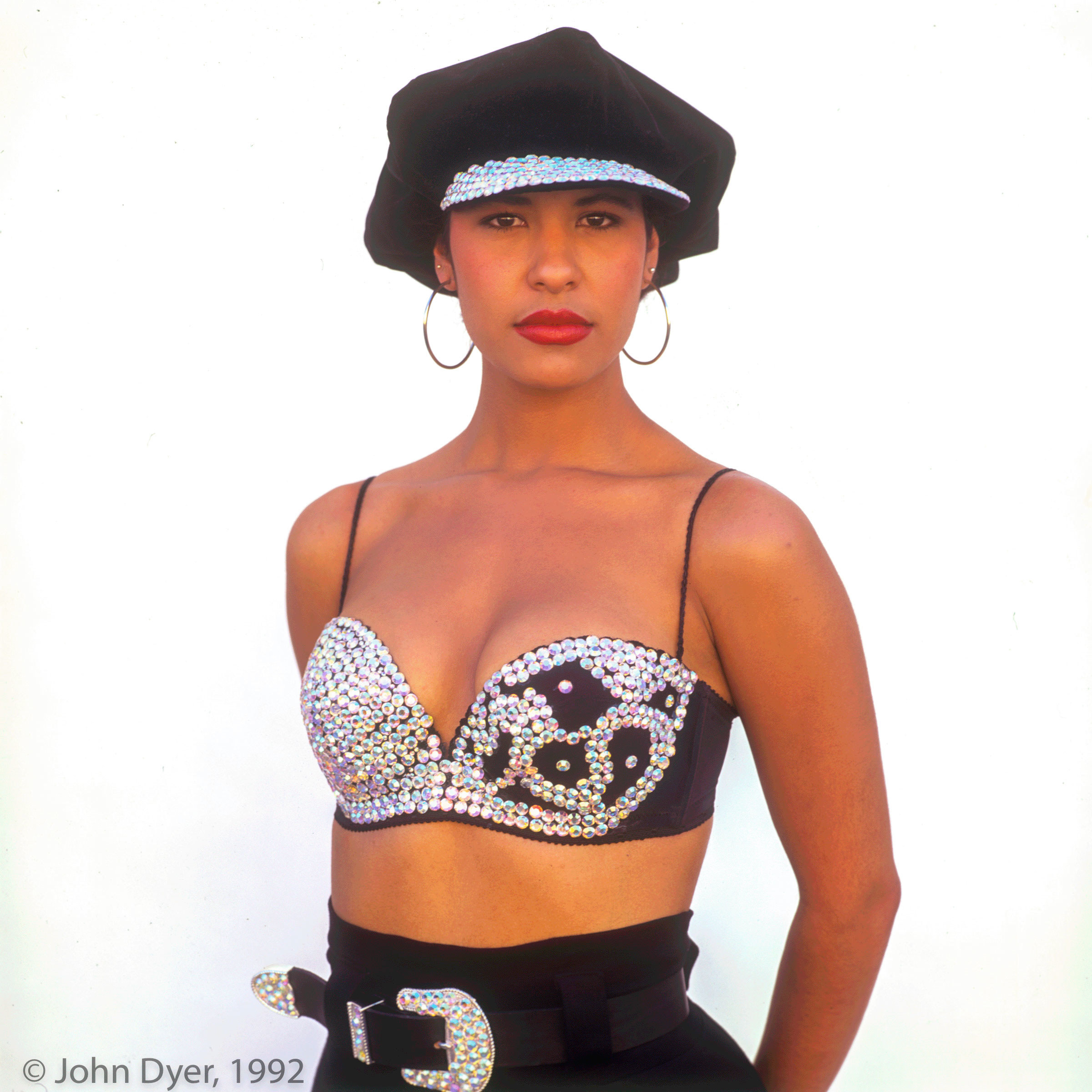 selena quintanilla posing for the camera while standing in front of a white backdrop