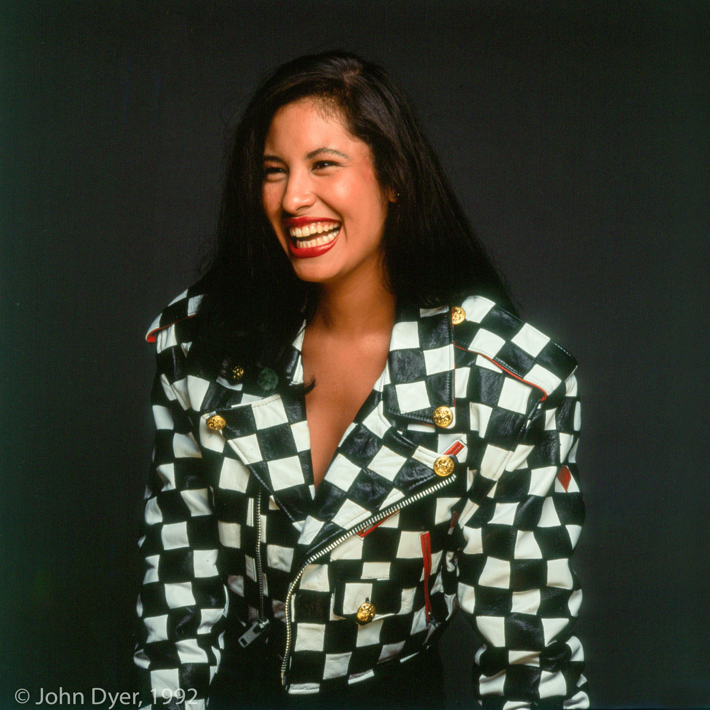 selena quintanilla laughing while having her photograph taken wearing a checked jacket