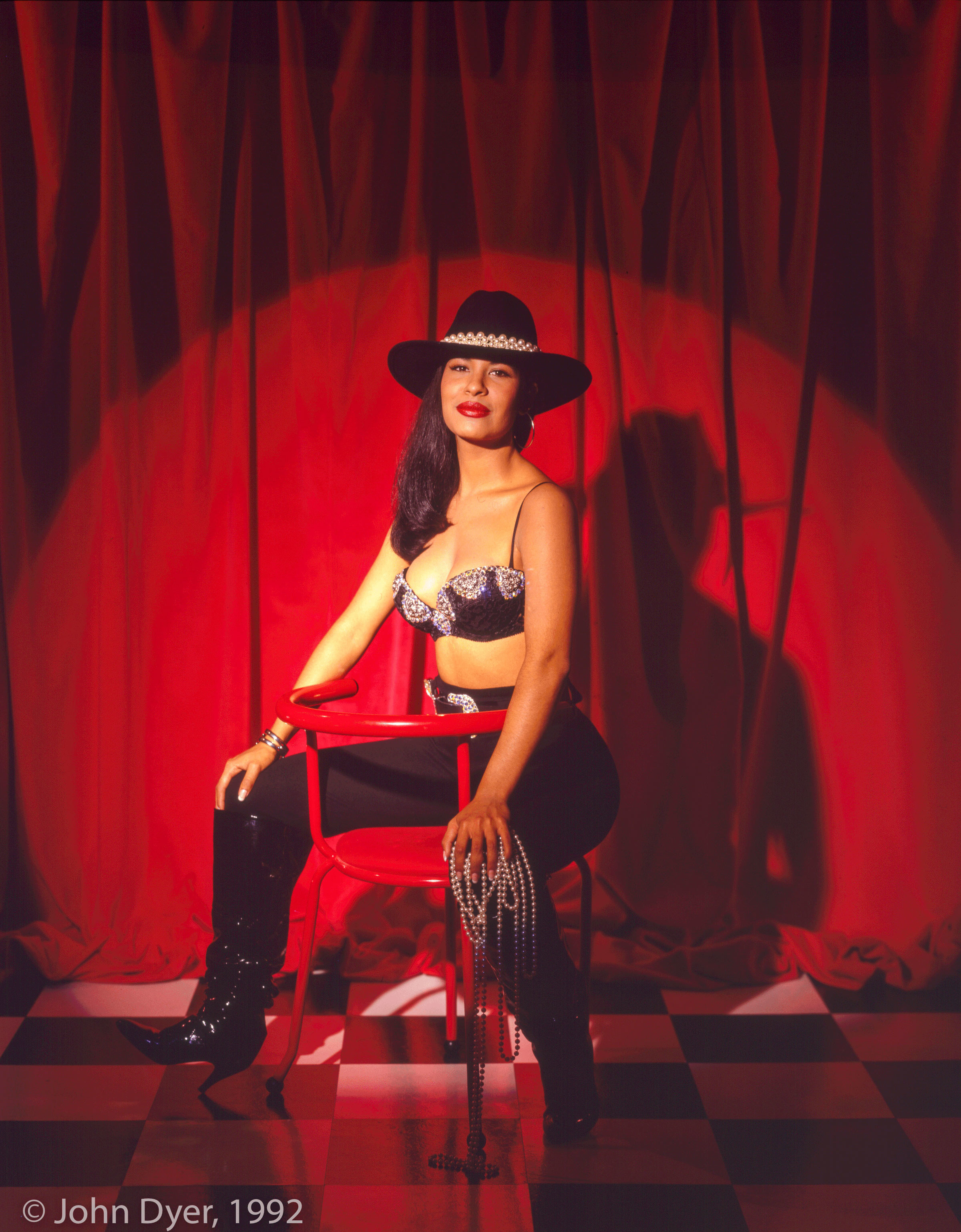 selena quintanilla smiling while sitting down for a photo