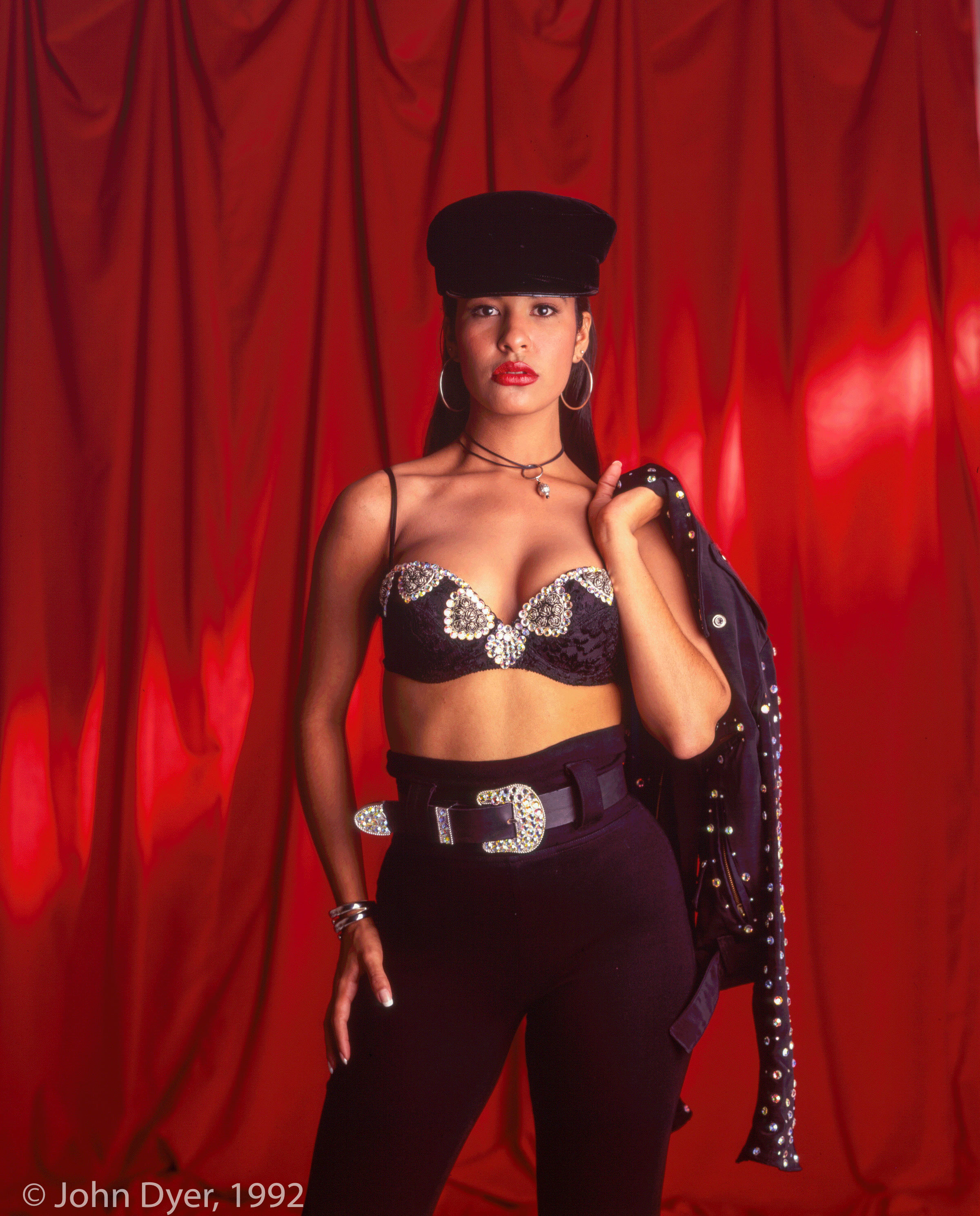 selena quintanilla posing for the camera while holding a jacket behind her