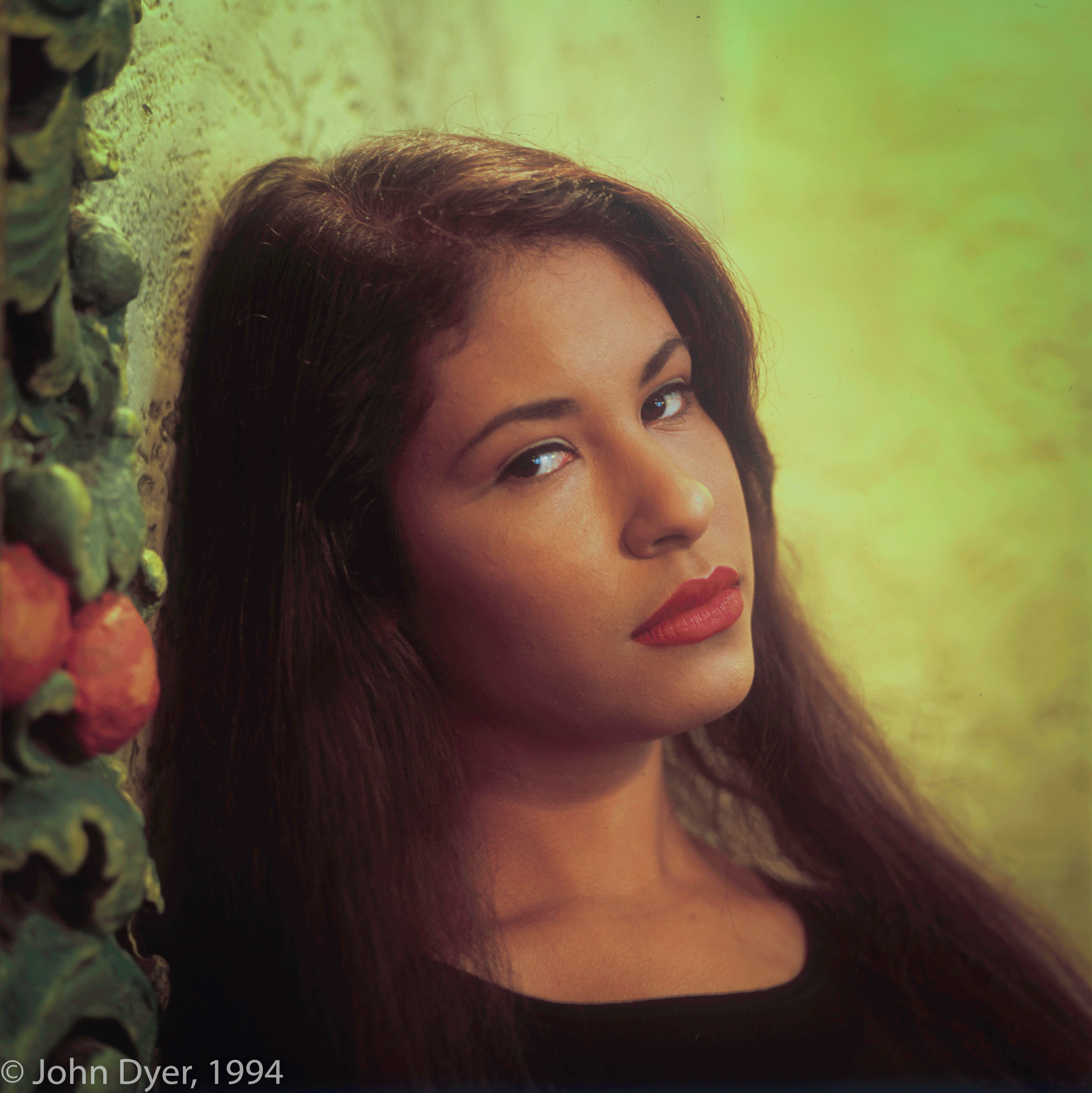 selena quintanilla looking directly into the camera for a photo while resting her head against a wall