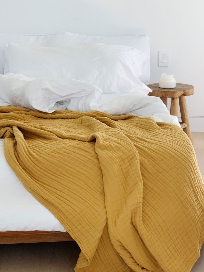The textured blanket in mustard, draped on a bed