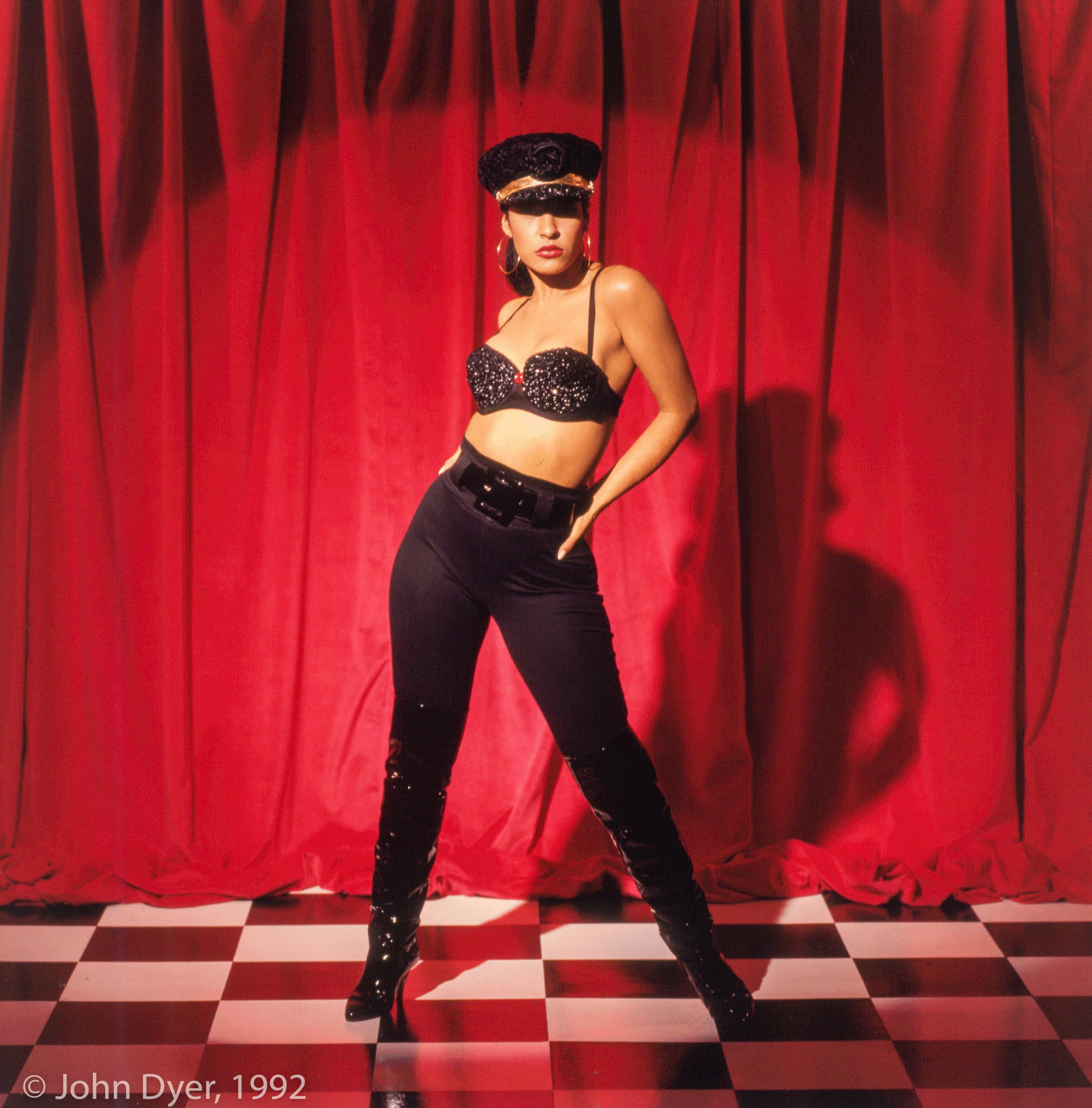 selena quintanilla posing for the camera whole standing on a checkered floor and red backdrop