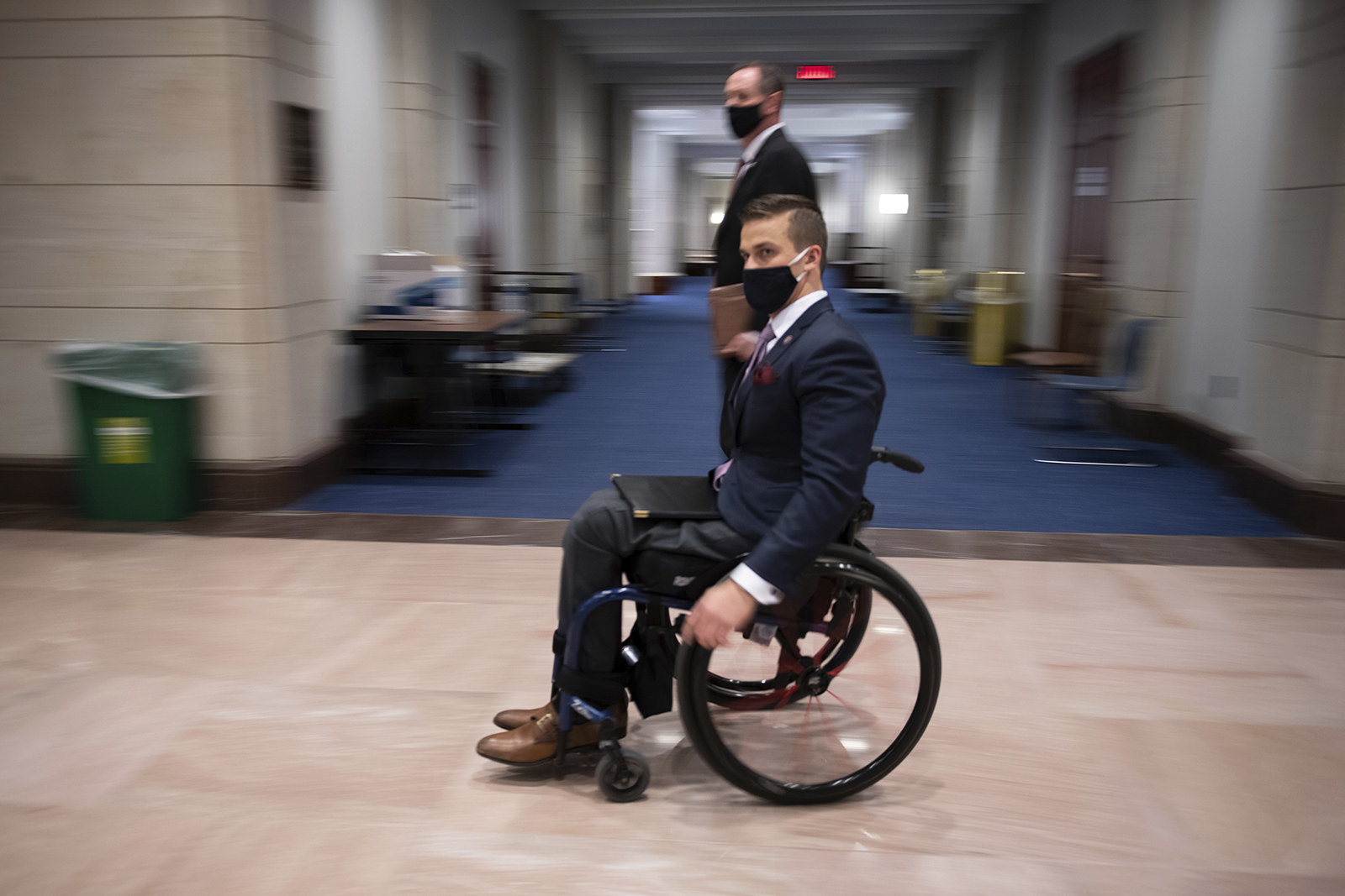 Cawthorn wears a suit and sits in a wheelchair against a blurred background in a Capitol corridor