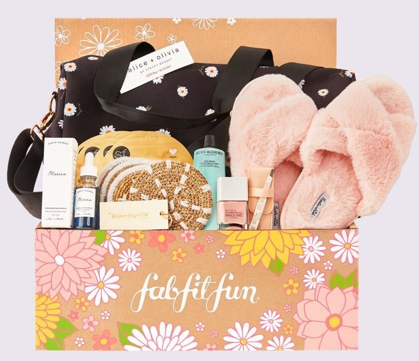a Fab Fit Fun box filled with soft pink slippers, coasters, beauty products, and other accessories