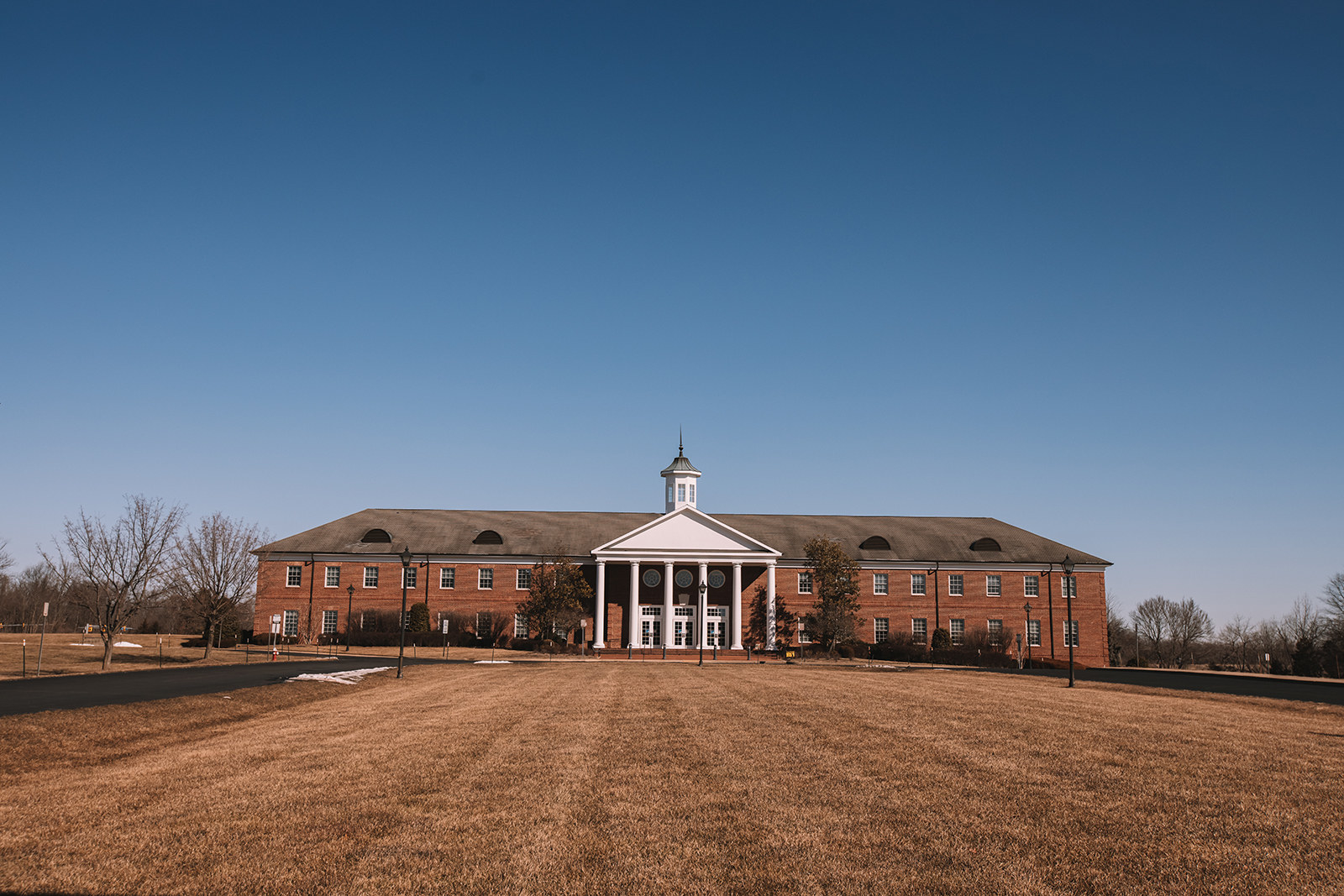 A large brick building with columns stands in the distance at the end of a grassy field