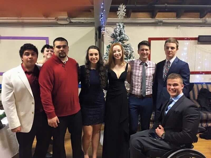 Eight people line up and pose in front of a Christmas tree
