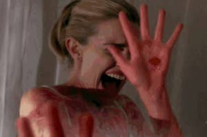 A girl with bloody hands shielding her face and screaming