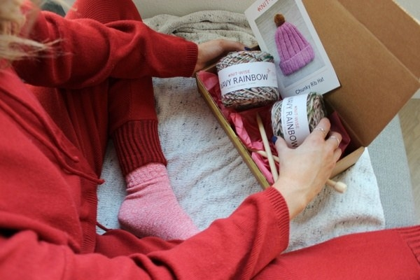 a model wearing pajamas and sitting next to the box filled with yarn