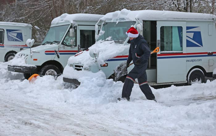 A mail truck covered in snow