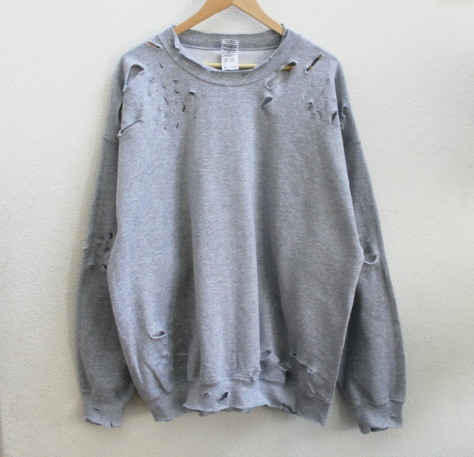 The grey sweatshirt with tears in the sleeves, hem, and neck