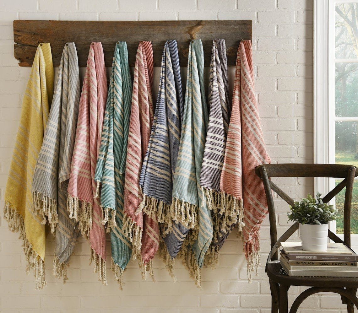 Several tasseled blankets hung up on a coat rack