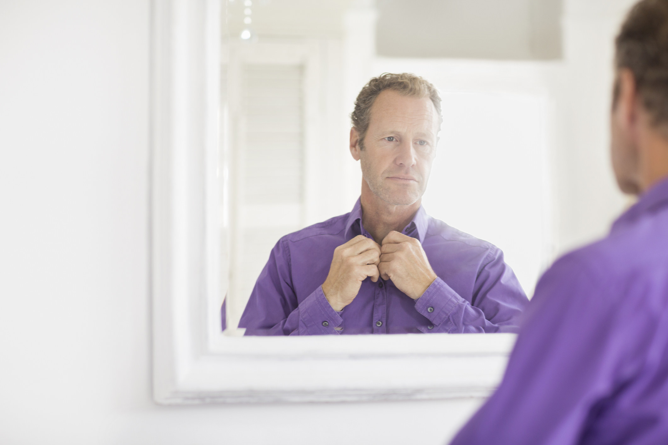 A man buttons up his purple shirt as he looks at himself in a mirror