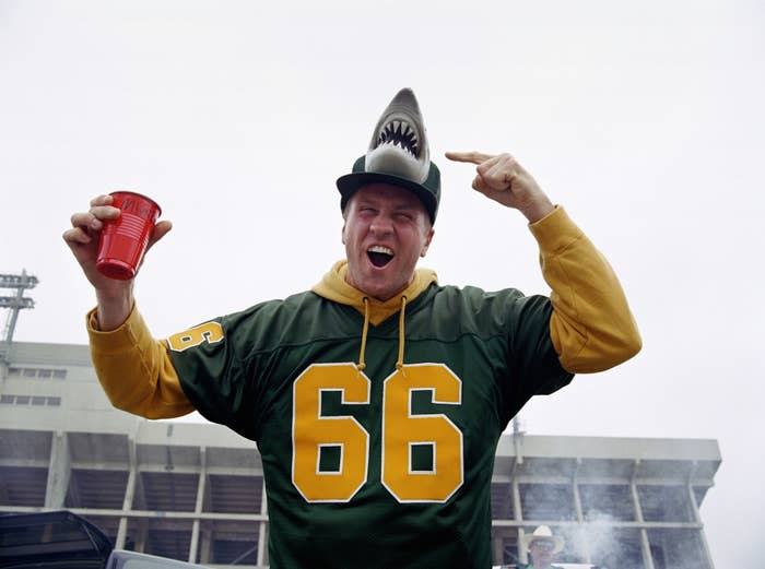 A tailgating football fan pointing at his baseball cap which has a shark head on top and holding a Solo cup