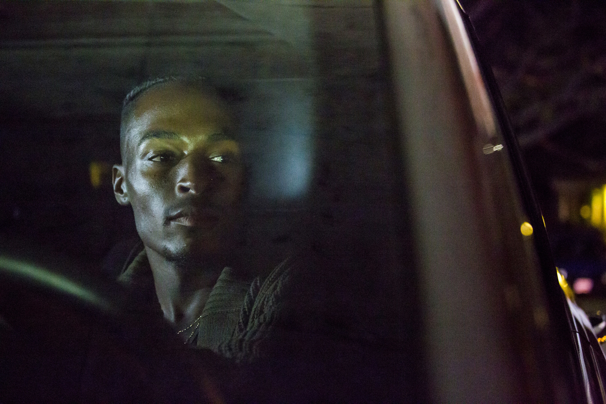 A man looks out the driver's side window of a car at night