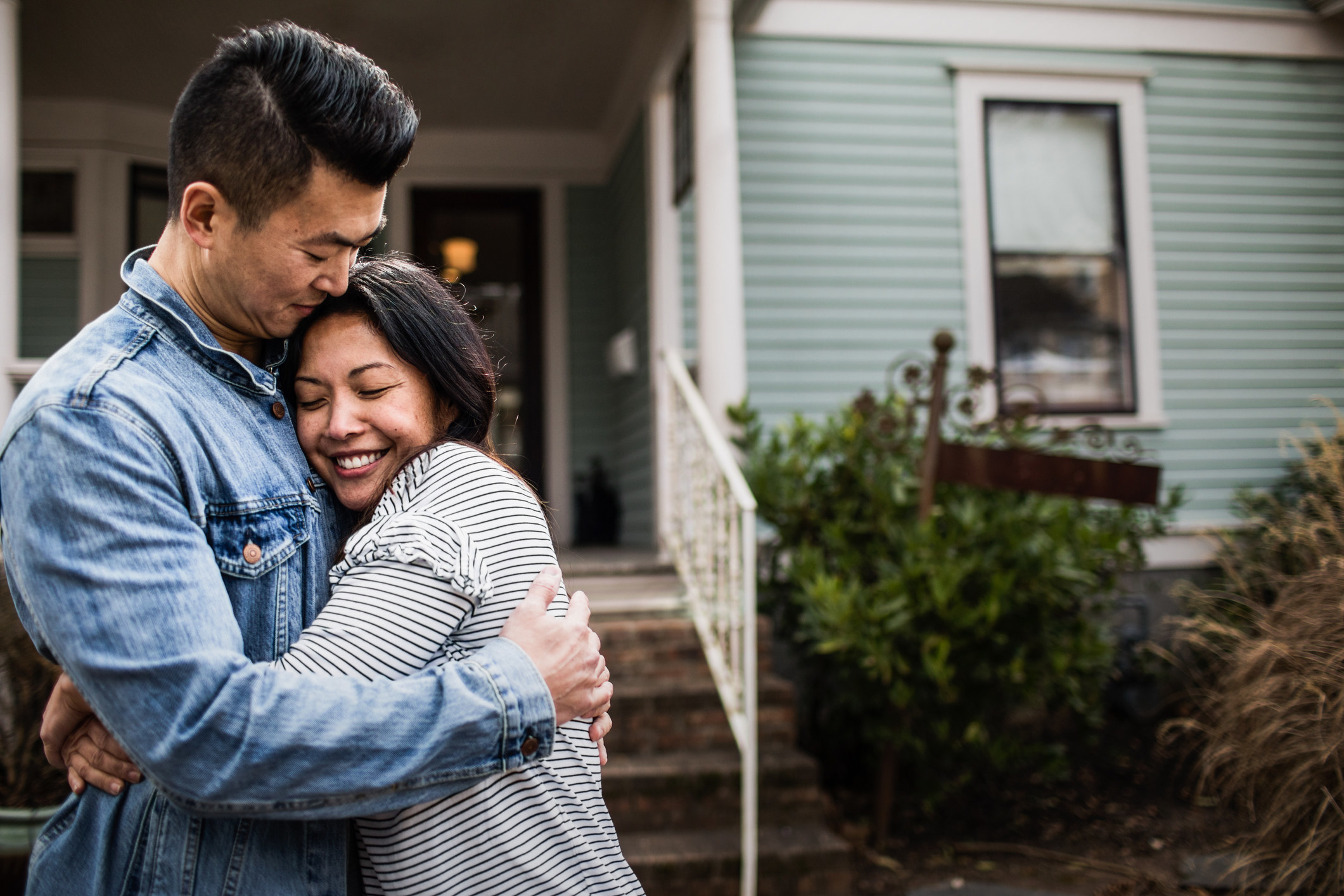 A couple embraces as they stand in front of a house