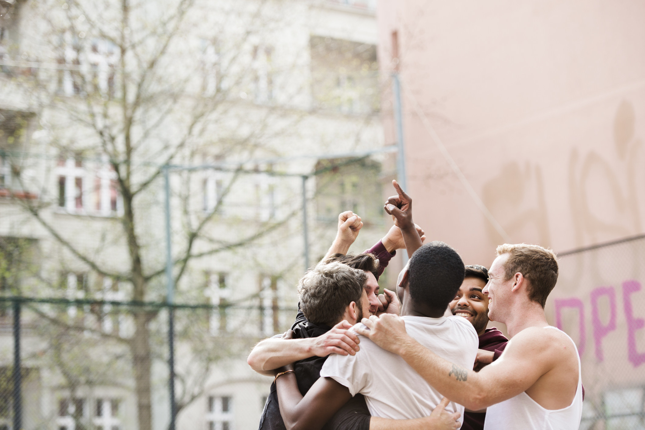 A group of men embracing on a basketball court