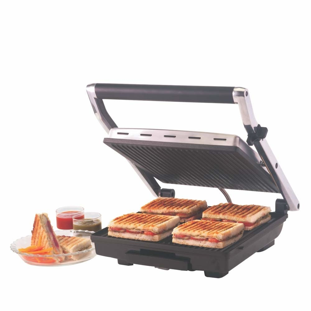 A grill with 4 sandwiches in it