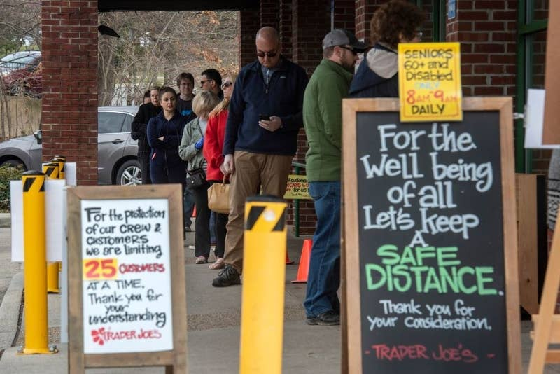 """A line of customers wait to enter a Trader Joe's store behind signs saying """"Let's keep a safe distance"""" and """"We are limiting 25 customers at a time"""""""
