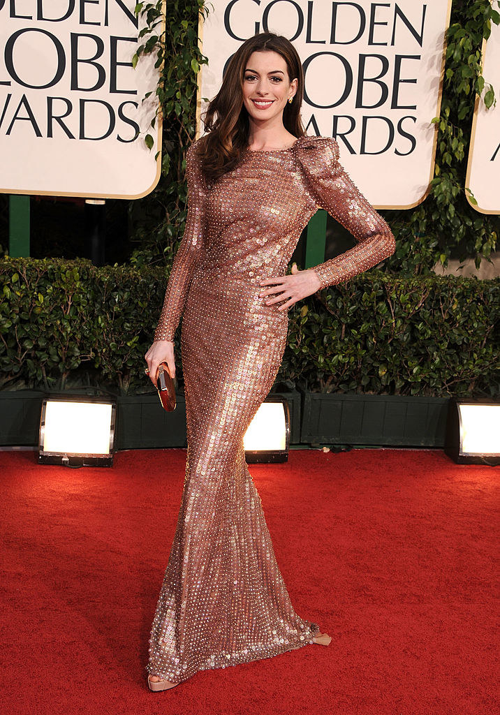 Anne with her hand on her hip as she shows off her metallic sequined gown with puffed shoulders