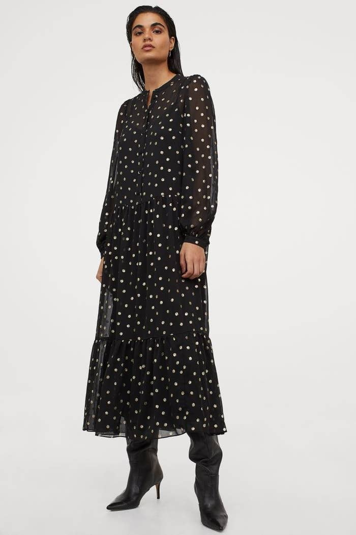 model wearing black and gold polka dotted dress with black boots