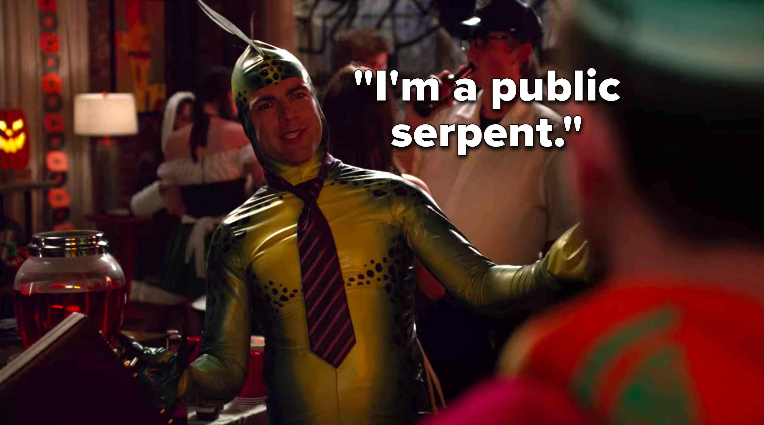 """Schmidt is dressed up in a snake costume with a tie and a briefcase and he says, """"I'm a public serpent"""""""