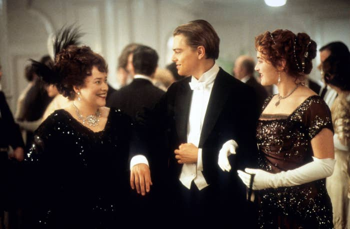 Kathy Bates, Leonardo DiCaprio, and Kate Winslet are arm-in-arm in the film Titanic