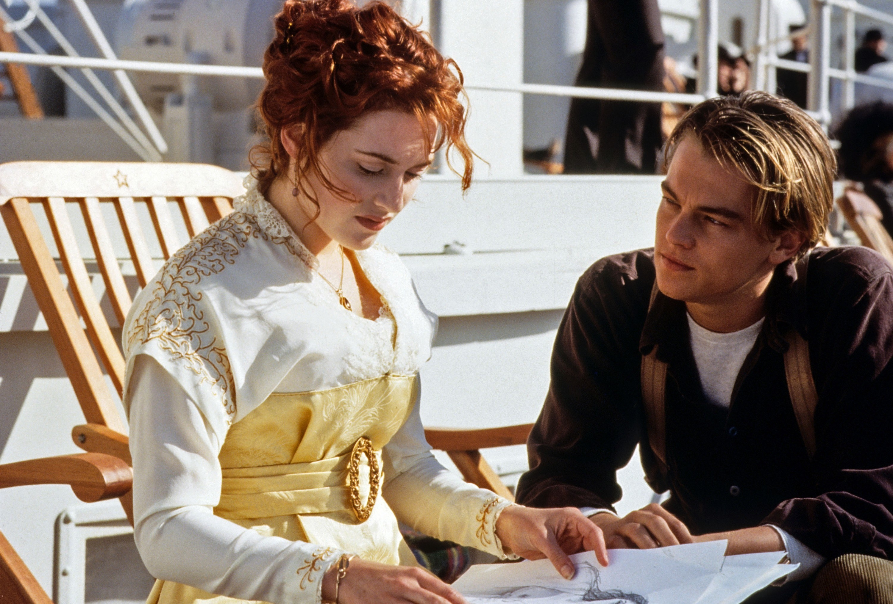 Kate Winslet shows Leonardo DiCaprio drawings while sitting down in a deck chair in the film Titanic