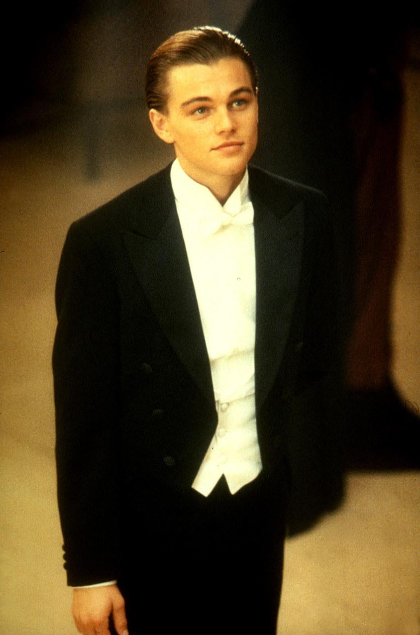 Leonardo DiCaprio stands while wearing a tuxedo in Titanic