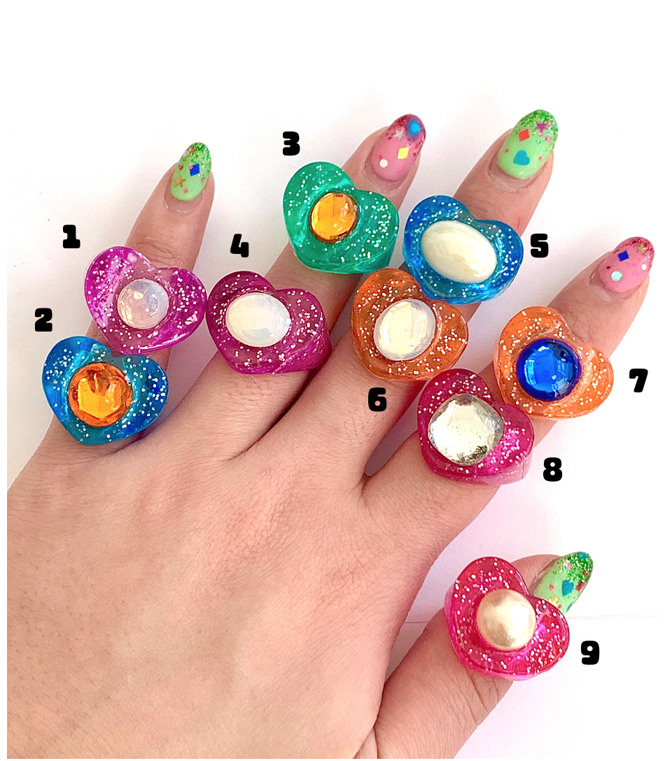 hand with various colored glitter lucky gems rings
