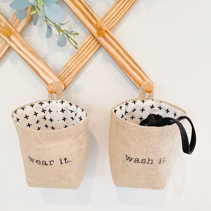 """Two baskets hanging from pegs on the wall with one that says """"wear it"""" and """"wash it"""""""