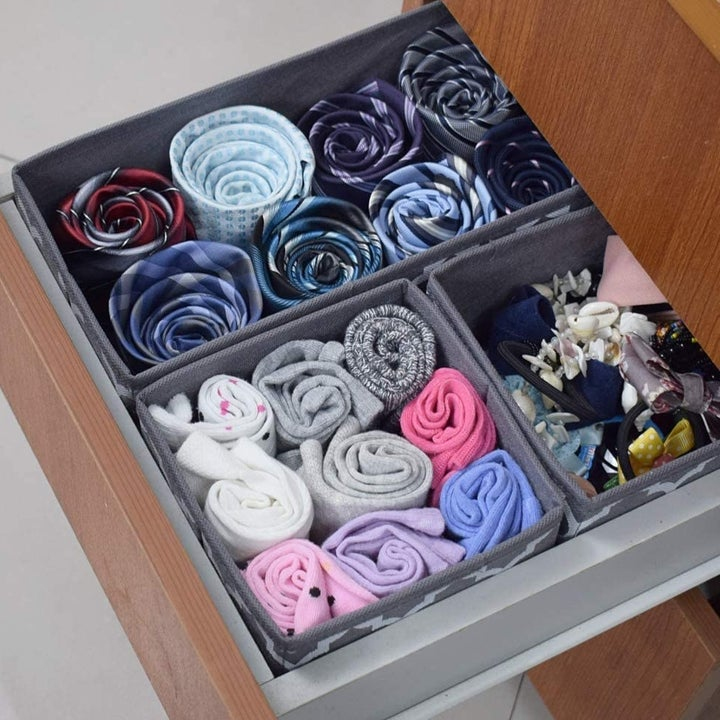 An open drawer with three different-sized drawer dividers inside filled with rolled-up clothes