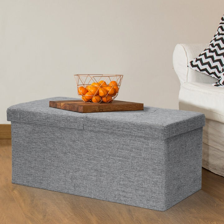 A light gray bench ottoman with a wooden tray and a bowl of oranges sitting on top