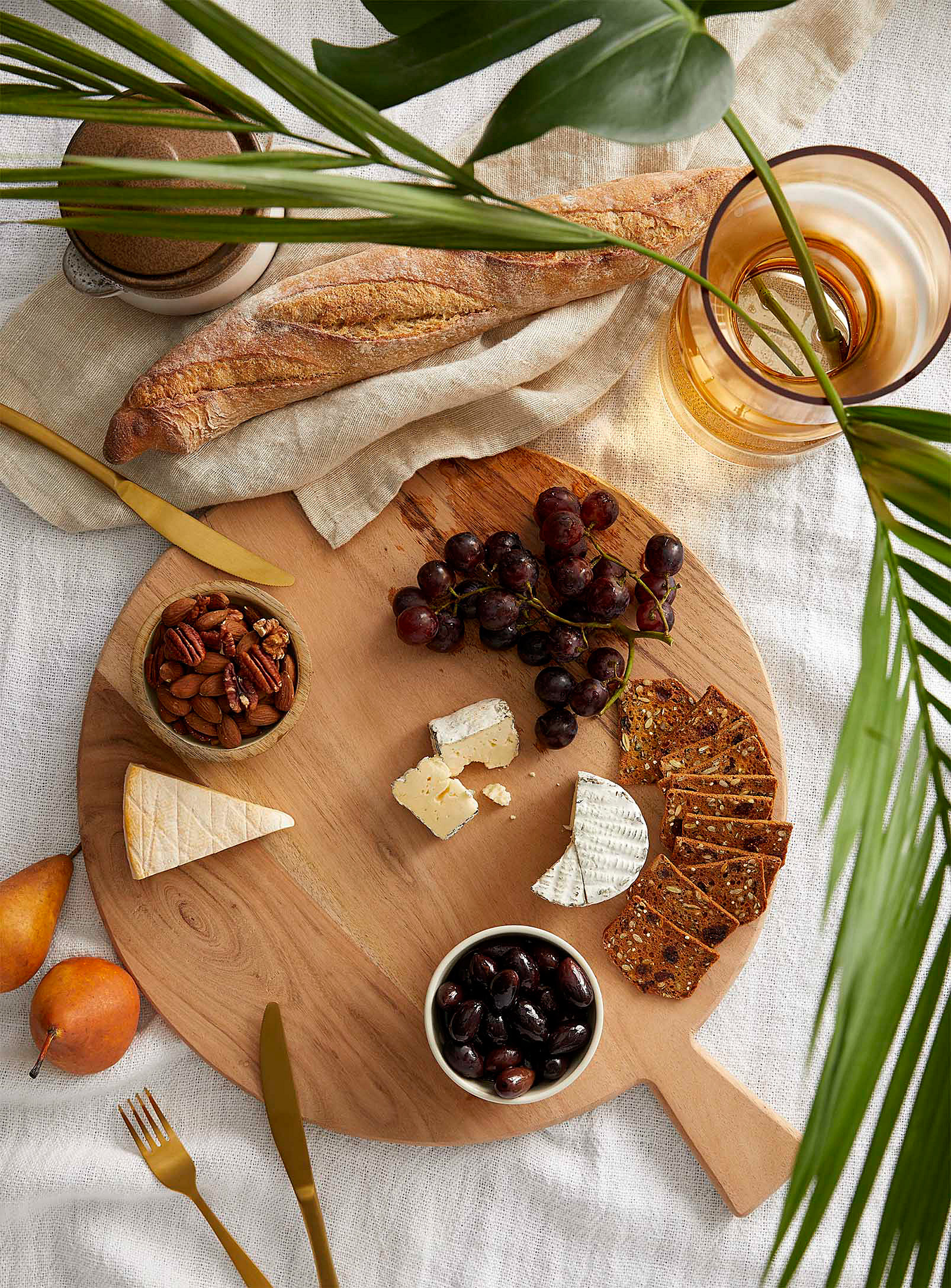 A round wooden tray with cheese, crackers, and grapes on it