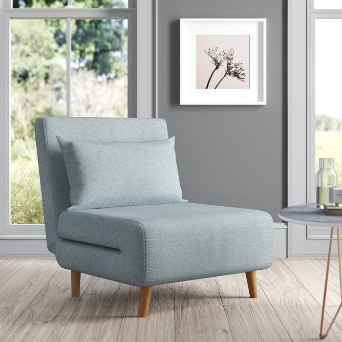 light gray chair that can fold out to a bed