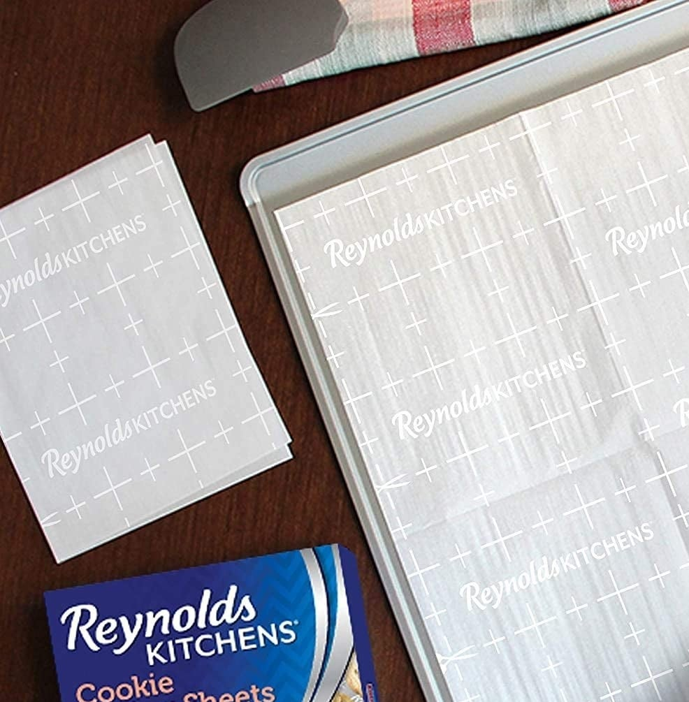 One sheet on a baking tray next to several folded sheets